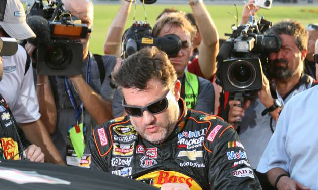 Tony Stewart climbs into his car to start a NASCAR Sprint Cup auto race at Atlanta Motor Speedway Sunday, Aug. 31, 2014, in Hampton, Ga. (AP Photo/Dale Davis)