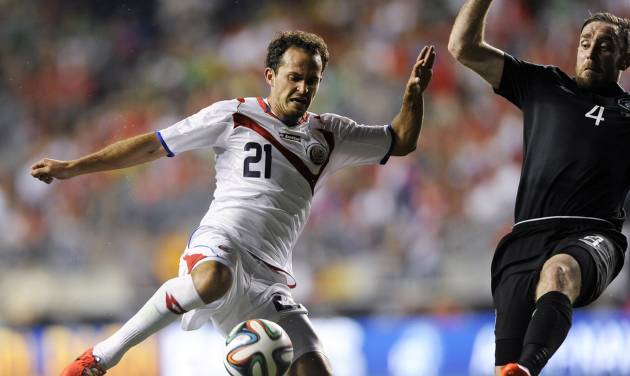 Costa Rica's Marco Urena (21) takes a shot on goal as Ireland's Richard Keogh defends during the second half of an international friendly soccer match on Friday, June 6, 2014, in Chester, Pa. The match ended in a 1-1 tie. (AP Photo/Michael Perez)