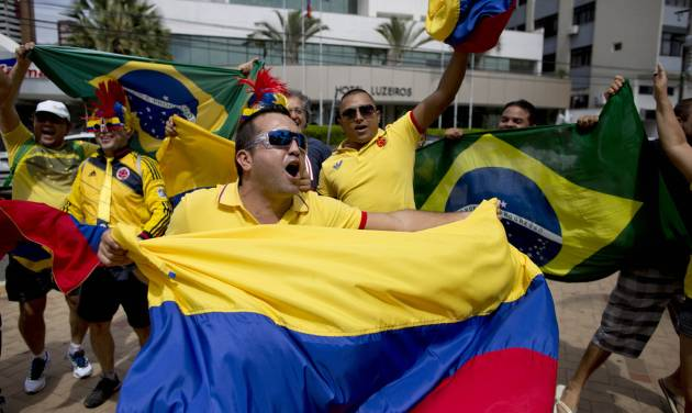 Fans of the Colombian national soccer team respond to television news cameras, waving their national flags, in front of the hotel where the Colombian national soccer team is staying in Fortaleza, Brazil, Thursday, July 3, 2014. Colombian supporters are in Fortaleza hoping to see some history being made in this northeastern World Cup city where Brazil and Colombia face off in the World Cup quarterfinals, Saturday. (AP Photo/Rodrigo Abd)