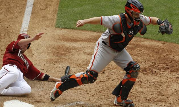 San Francisco Giants' Buster Posey (28) takes a throw wide of home plate as Arizona Diamondbacks' Aaron Hill slides in to score during the seventh inning in an MLB baseball game Sunday, April 8, 2012, in Phoenix.(AP Photo/Ross D. Franklin)