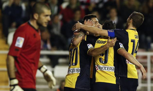Atletico's Arda Turan, center left, celebrates his goal with teammates during the Spanish La Liga soccer match between Rayo Vallecano and Atletico de Madrid at the Vallecas stadium in Madrid, Spain, Sunday, Jan. 26, 2014. (AP Photo/Andres Kudacki)