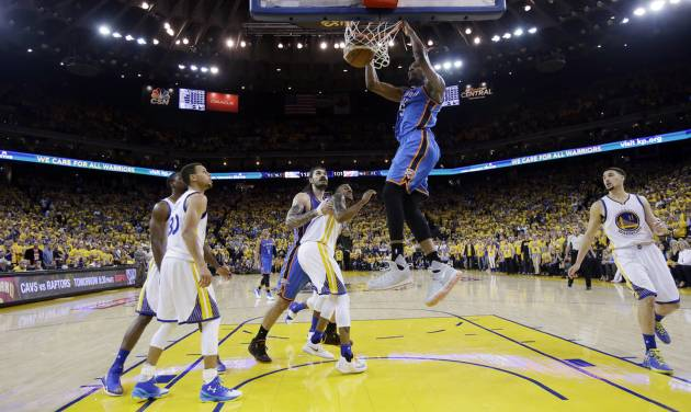 Oklahoma City Thunder\'s Kevin Durant, center, dunks against the Golden State Warriors during...