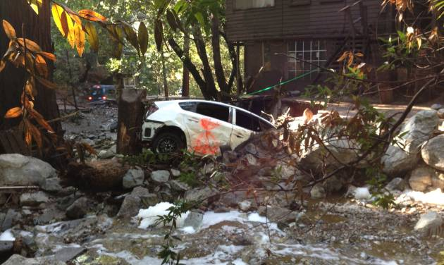 A car is lodged in the debris on Monday, Aug. 4, 2014 where a body that was swept into the rain-swollen water course was found Sunday in Mount Baldy, Calif. About 2,500 people were stranded early Monday after thunderstorms caused mountain mudslides in Southern California. (AP Photo/Brian Melley)
