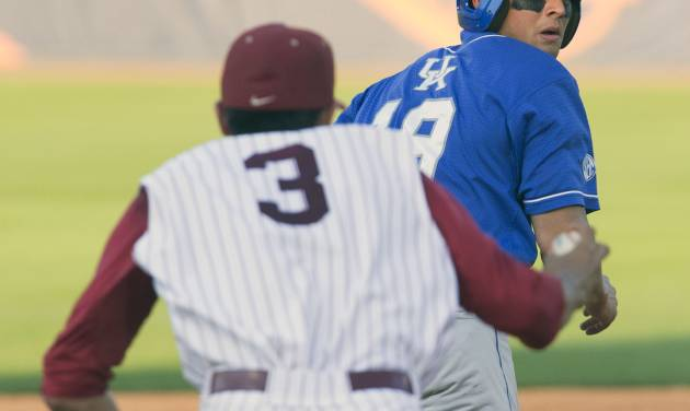 Kentucky's Austin Cousino looks back at a charging Alabama's Daniel Cucjen as he is caught between second and third during the Southeastern Conference NCAA college baseball tournament, Tuesday, May 20, 2014, in Hoover, Ala. (AP Photo/Hal Yeager)