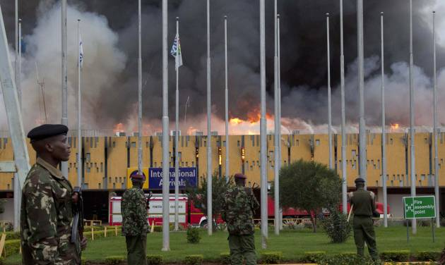 FILE - In this Wednesday, Aug. 7, 2013 file photo, police stand guard as fire engulfs the international arrivals unit of the Jomo Kenyatta International Airport, in Nairobi, Kenya.   Putting that disaster in the past , Kenya Airways' chief executive Titus Naikuni is predicting an exciting couple of years for African air travel, with new Boeing Dreamliners, the opening of a new terminal and, on the horizon, Kenya's first direct flights to the United States.(AP Photo/Sayyid Azim, File)