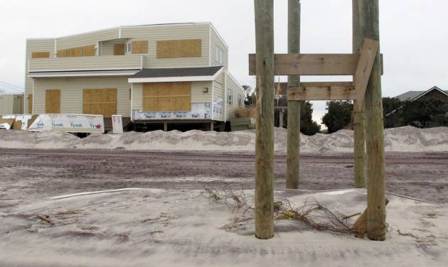 In this Friday, Nov. 16, 2012 photo, pilings that once held a walkway over dunes leading to the beach are all that remain outside a boarded up home in Ocean Beach, N.Y. The Fire Island community was damaged in Superstorm Sandy. (AP Photo/Frank Eltman)