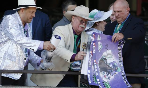 California Chrome co-owner Steve Coburn, center, reaches for posters to before the Belmont Stakes horse race, Saturday, June 7, 2014, in Elmont, New York. (AP Photo/Kathy Willens)