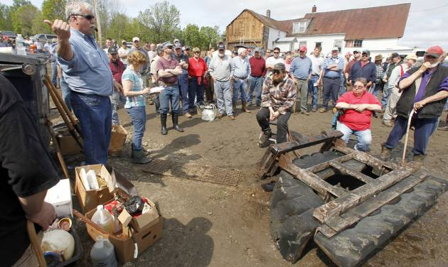 In this May 16, 2012 photo, auctioneer Ron Wright, left, auctions farm equipment at the MacLaren farm in Plainfield, Vt. The MacLarens have faced hardships in the family's 70-plus years farming the same land in Plainfield. But another drop in milk prices this spring combined with soaring feed and fuel costs is forcing the third generation to give up dairy farming. (AP Photo/Toby Talbot)