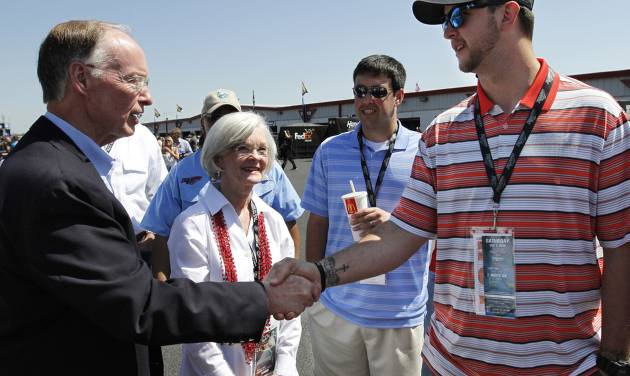 Former Alabama Quarterback AJ McCarron, right, shakes the hand of Alabama Gov. Robert J. Bentley as Alabama first lady Dianne Jones Bentley looks on before the NASCAR Aaron's 499 Sprint Cup series auto race at Talladega Superspeedway, Sunday, May 4, 2014, in Talladega, Ala. (AP Photo/Butch Dill)