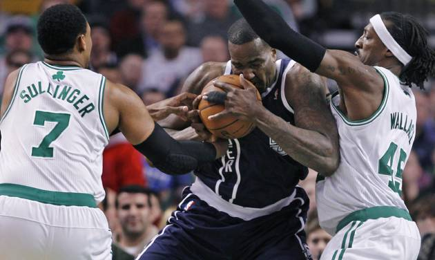 Oklahoma City Thunder center Kendrick Perkins, center, is sandwiched between Boston Celtics center Jared Sullinger (7) and forward Gerald Wallace on a drive to the basket during the first quarter of an NBA basketball game in Boston, Friday, Jan. 24, 2014. (AP Photo/Charles Krupa)