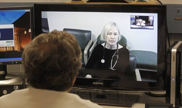 In this Thursday, Dec. 20, 2012 photo, Dr. Terry Rabinowitz, back to camera, talks with nurse Leslie Orelup at Helen Porter Nursing Home on in Burlington, Vt. New health insurance regulations in Vermont are giving a boost to telemedicine, the system that enables health care providers to offer consult with patients without being in the same room. Telemedicine isn't new, but the new regulations make it easier for physicians to be reimbursed for services performed by two-way video hookups. Fletcher Allen Telemedicine director Dr. Terry Rabinowitz says popular specialties are psychiatry and dermatology. (AP Photo/Toby Talbot)