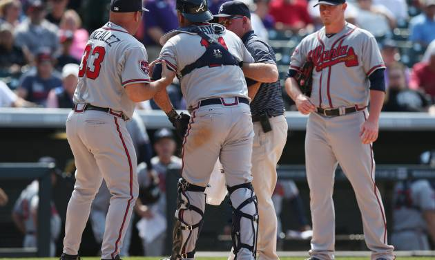 Atlanta Braves manager Fredi Gonzalez, left, helps catcher Gerald Laird, center, off the field with trainer Jeff Porter as relief pitcher David Carpenter looks on against the Colorado Rockies in the eighth inning of the Rockies' 10-3 victory in a baseball game in Denver on Thursday, June 12, 2014. Laird was hit in the face by rockies batter Corey Dickerson as he was swinging at a pitch. The play acted as a catalyst for the ejection of Rockies' manager Walt Weiss after Dickerson was hit by a pitch when action resumed. (AP Photo/David Zalubowski)