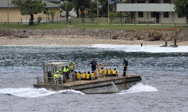 In this photo taken on April 14, 2013, a group of Vietnamese asylum seekers are taken by barge to a jetty on Australia's Christmas Island. Nearly 40 years after hundreds of thousands of Vietnamese fled the country's Communist regime by boat, a growing number are taking to the water again. The latest boat carrying Vietnamese cruised into Australia's Christmas Island one morning last month, according to witnesses on the shore. (AP Photo)