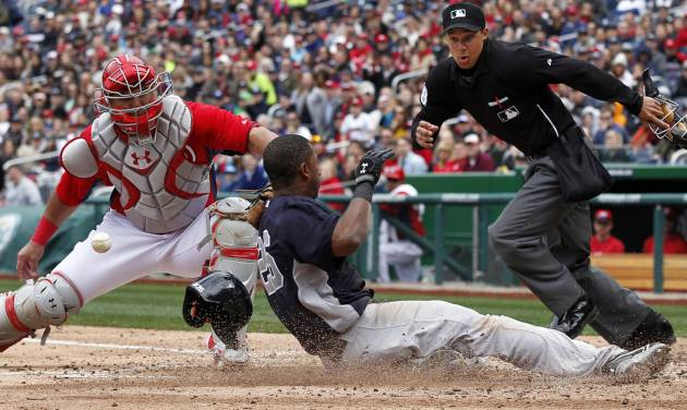 Washington Nationals catcher Wilson Ramos loses the ball as New York Yankees' Eduardo Nunez slides safely into home with home plate umpire Adam Hamari looking on at right during the fourth inning of an exhibition baseball game at Nationals Park Friday, March 29, 2013, in Washington. (AP Photo/Alex Brandon)