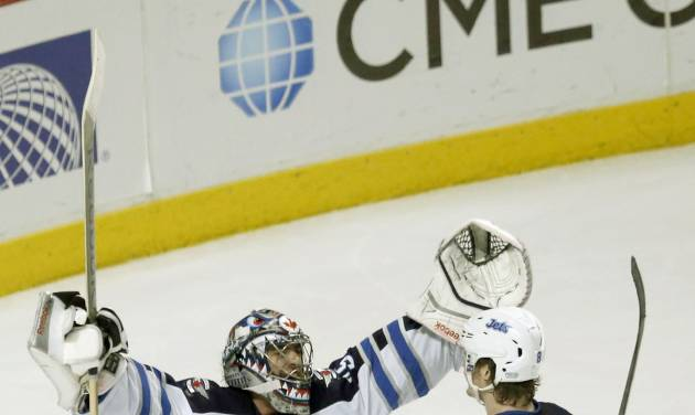 Winnipeg Jets goalie Al Montoya celebrates the Jets' 3-1 win over the Chicago Blackhawks with Jacob Trouba after an NHL hockey game Sunday, Jan. 26, 2014, in Chicago. (AP Photo/Charles Rex Arbogast)