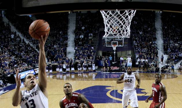 Kansas State guard Angel Rodriguez (13) gets past Oklahoma guard/forward Cameron Clark (21) to put up a shot during the second half of an NCAA college basketball game on Saturday, Jan. 19, 2013, in Manhattan, Kan. Kansas State won the game 69-60. (AP Photo/Charlie Riedel)