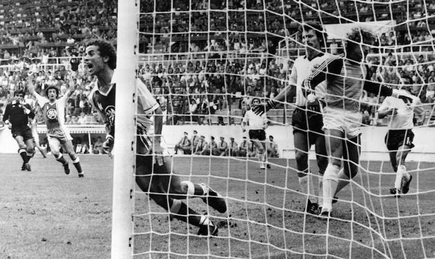 FILE - In this June 16, 1982 file photo, Algeria's Lakhdar Belloumi, left, celebrates after scoring the second and winning goal for his team during the World Cup soccer match between Algeria and West Germany in Gijon, Spain. On this day: Algeria beats West Germany 2-1 in one of the great upsets in World Cup history. (AP Photo/File)