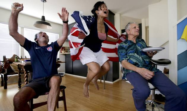 FILE - In this Sunday, June 22, 2014 file photo, Ed Pollard, left, Tina Termsomket and John Courte react after Portugal scored against USA during the first half while watching a televised group G World Cup soccer match at a watch party in Newport Beach, Calif. The match was almost certainly the most-watched soccer game ever in the U.S., an emphatic confirmation of the sport's rising popularity in a country slower to embrace it than the rest of the world. (AP Photo/Chris Carlson, File)