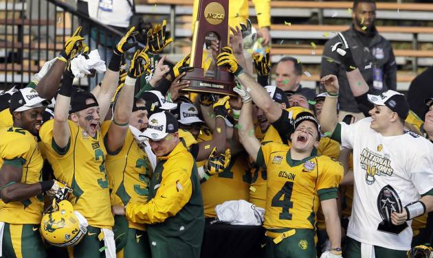 FILE – In this Jan. 4, 2014 file photo, North Dakota State players celebrate with the trophy after beating Towson 35-7 in the FCS championship NCAA college football game in Frisco, Texas. The poll of league coaches, media and sports information directors released Tuesday, July 29, 2014, has NDSU picked to win the Missouri Valley Football Conference title this season. South Dakota State is picked to finish second in the conference. (AP Photo/Tony Gutierrez, File)