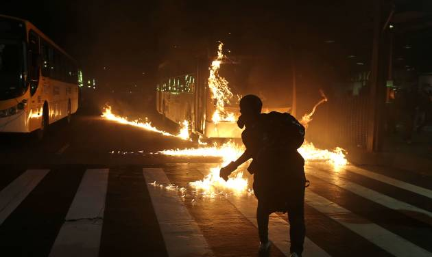 A demonstrator from the Black Bloc anarchist group throws a Molotov cocktail at a burning bus during a protest against Sao Paulo's Governor Geraldo Alckmin in Sao Paulo, Brazil, Friday, Oct. 25, 2013. Protesters are demanding a free public transportation system. (AP Photo/Andre Penner)