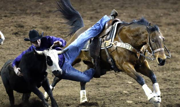 Jason Stewart of Bristow, Okla., rides Stevie in the steer wrestling competition during the International Finals Rodeo at the State Fair Arena in Oklahoma City, Friday, Jan. 17, 2014.  Photo by Sarah Phipps, The Oklahoman