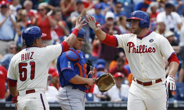 Philadelphia Phillies' Darin Ruf, right, and Carlos Ruiz, left, celebrate in front of  New York Mets catcher Anthony Recker after Ruff's two-run home run during the fourth inning of a baseball game, Monday, Aug. 11, 2014, in Philadelphia. (AP Photo/Matt Slocum)