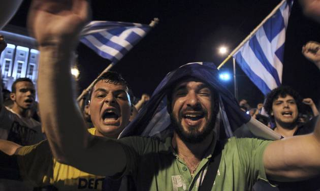 Greece soccer supporters celebrate their team's win in a World Cup soccer match in front of the city's landmark of White Tower, in the northern Greek port of Thessaloniki, on Wednesday, June 25, 2014. Greece won Ivory Coast 2-1 to advance to the round of 16 for the first time in their World Cup history. (AP Photo/Nikolas Giakoumidis)
