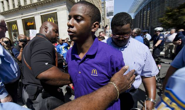 A McDonald's worker is detained by police during a protest to push fast-food chains to pay their employees at least $15 an hour, outside a McDonald's restaurant Thursday, Sept. 4, 2014, in Philadelphia. The protest movement, which is backed financially by the Service Employees International Union and others, has gained national attention at a time when the wage gap between the poor and the rich has become a hot political issue. (AP Photo/Matt Rourke)