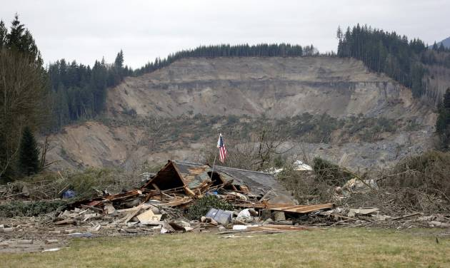 A flag, put up by volunteers helping search the area, stands in the ruins of a home left at the end of a deadly mudslide from the now-barren hillside seen about a mile behind, Tuesday, March 25, 2014, in Oso, Wash. At least 14 people were killed in the 1-square-mile slide that hit in a rural area about 55 miles northeast of Seattle on Saturday. Several people also were critically injured, and homes were destroyed. (AP Photo/Elaine Thompson)