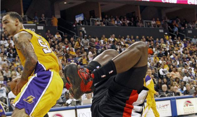 Portland Trail Blazers forward J.J. Hickson, right, goes flying after colliding with Los Angeles Lakers center Robert Sacre in an NBA basketball preseason game in Ontario, Calif., Wednesday, Oct. 10, 2012. (AP Photo/Reed Saxon)