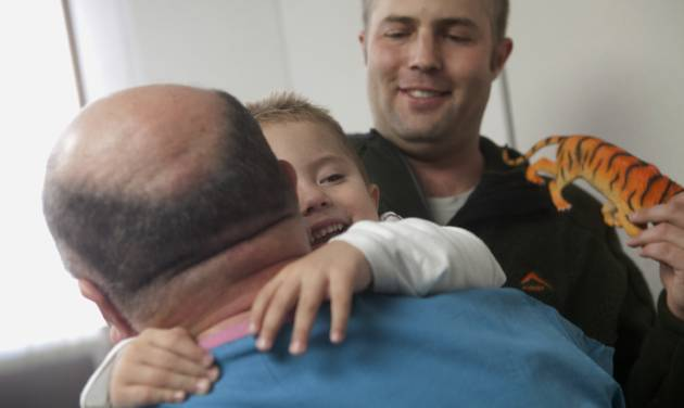 Andre de Guisti, 2, from Johannesburg, South Africa, hugs Dr. Anthony de Bari on Wednesday, Jan. 9, 2013 at Covenant HealthCare in Saginaw, Mich. Dr. de Bari operated on de Guisti two years ago when he heard from a fellow doctor who traveled to South Africa for a hunting trip about a boy born with an abnormal development of the lower spine. Doctors in South Africa said the only option was to amputate Andre's legs, but when Dr. de Bari, who has three patients in Saginaw with the same condition, heard about Andre, he offered to help. The de Guistis flew to Saginaw and Andre received surgery the same week. Despite a lot of physical therapy ahead of him de Bari is surprised at how well Andre has improved and expects him to be able to walk. (AP Photo/The Saginaw News, Clay Lomneth )