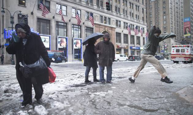 Pedestrians attempt to traverse slush puddles near Pennsylvania Station, Thursday, Feb. 13, 2014, in New York. Snow and sleet are falling on the East Coast, from North Carolina to New England, a day after sleet, snow and ice bombarded the Southeast. (AP Photo/John Minchillo)
