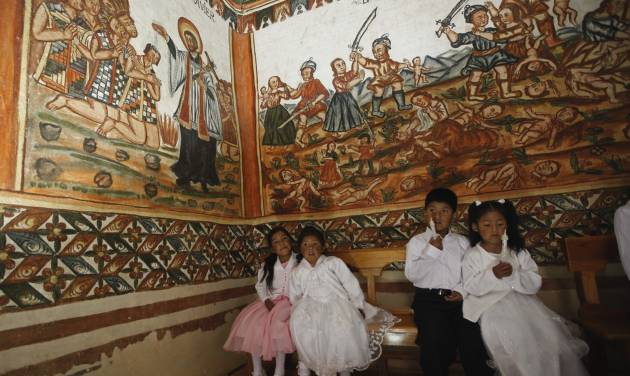 Children wait te be baptized inside the Sistine Chapel of Los Andes in Curahuara de Carangas, Oruro department, 260 km. (160 miles) south from La Paz, Bolivia, Saturday, Dec. 8, 2012.  The colonial-era house of worship known in Bolivia as the Sistine Chapel of the Andes was filled with flowers over the weekend for those celebrating two weddings and seven baptisms on the wind swept mountain plateau.(AP Photo/Juan Karita)