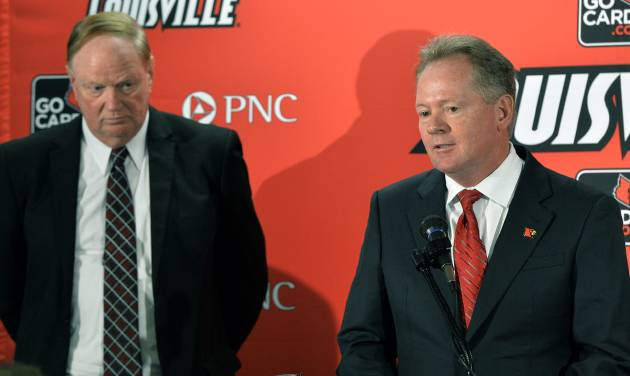 Bobby Petrino, right, address reporters as University of Louisville President D. James R. Ramsey looks on following the announcement of Petrino's hiring as football coach, Thursday, Jan. 9, 2014, at Papa John's Cardinal Stadium in Louisville, Ky. (AP Photo/Timothy D. Easley)