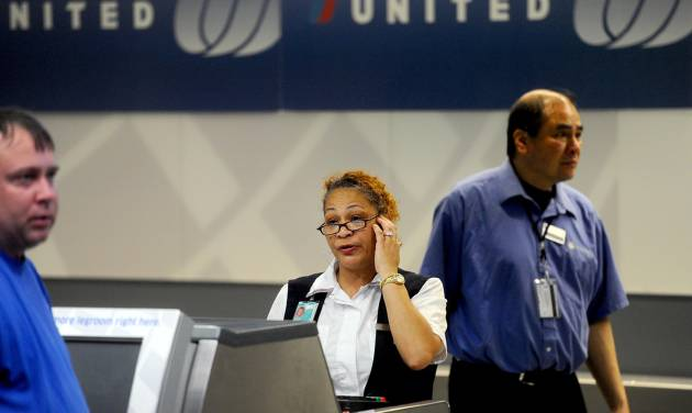 FILE - In this Friday, June 17, 2011, file photo, a United Airlines employee staffs a ticketing counter at San Francisco International Airport, in San Francisco. United Airlines said, Jan. 16, 2014, it will furlough 688 flight attendants after it didn't get enough people to take a voluntary buyout. (AP Photo/Noah Berger, File)