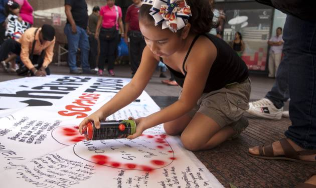 A young girl spraypaints red dots on her message of encouragement for Venezuela's President Hugo Chavez, outlined with a heart, on a giant poster, in Caracas, Venezuela, Friday, Dec. 14, 2012.  Somber confidants of Chavez say he is going through a difficult recovery after cancer surgery in Cuba, and one close ally is warning Venezuelans that their leader may not make it back for his swearing-in next month. (AP Photo/Ariana Cubillos)