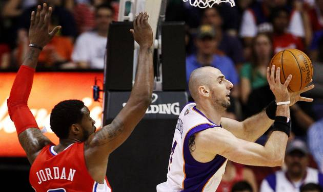 Phoenix Suns' Marcin Gortat, of Poland, passes around Los Angeles Clippers' DeAndre Jordan (6) during the first half of an NBA basketball game, Thursday, April 19, 2012, in Phoenix. (AP Photo/Matt York)
