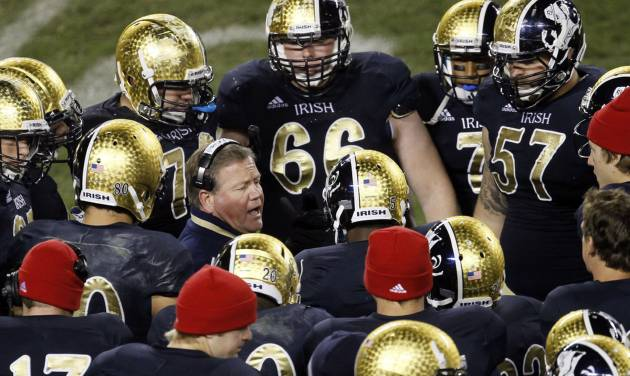 "FILE - In this Oct. 6, 2012, file photo, Notre Dame head coach Brian Kelly, center left, talks to his team during the second half of an NCAA college football game against Miami at Soldier Field in Chicago. About the only thing the Irish haven't done yet this season is rally from behind to win. The Irish have been able to ignore what coach Kelly refers to as the ""noise"" so far, but it keeps getting louder with every victory.(AP Photo/Charles Rex Arbogast, File)"