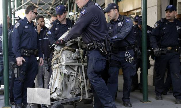 Officials remove a plane part that was discovered wedged between an apartment building and a mosque in New York, Wednesday, May 1, 2013. Authorities believe the plane part is from one of the two hijacked airliners that brought down the trade center on Sept. 11, 2001. (AP Photo/Seth Wenig)