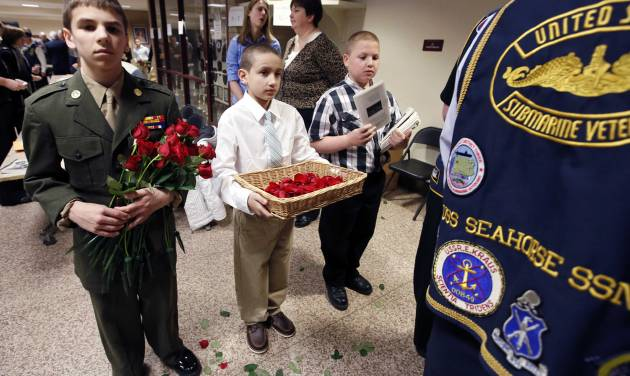 Josh Royer, 14, of Stratham, N.H., left, Alex Cardona, 11, of York, Maine, center, and Alex Coulombe, 11, of Freemont, N.H., offer roses and programs before a service marking the 50th anniversary of the sinking of the USS Thresher, Saturday, April 6, 2013, at the high school in Portsmouth, N.H. (AP Photo/Michael Dwyer)