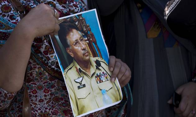 A supporter of former Pakistani President Pervez Musharraf holds a photo of him outside the special court in Islamabad, Pakistan, Monday, March 31, 2014. A special Pakistani court Monday indicted former military ruler Musharraf on five counts of high treason, marking a sharp blow to the country's powerful military. (AP Photo/B.K. Bangash)