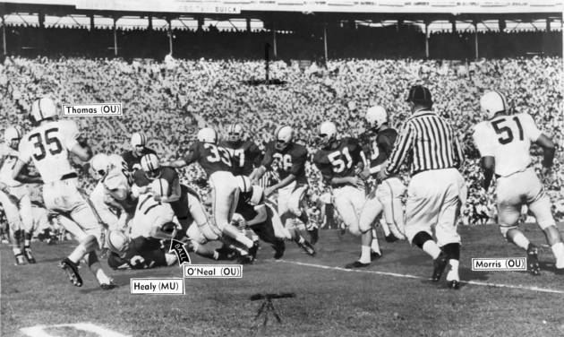 OU quarterback Jay O'Neal is brought to the end of a five-yard gain by Terrapin Don Healy and a host of Maryland defenders during the first period of Monday's Orange Bowl classic. Photo taken by Joe Miller. Date photo was taken unknown. Photo was published in The Daily Oklahoman on 1-3-1956.