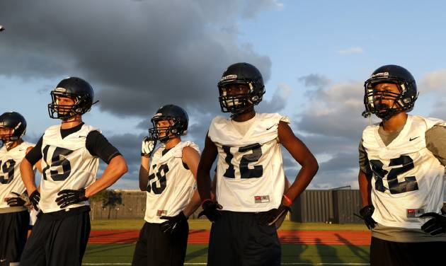 Player line up during drills at the first football practice for Southmoore High School, Tuesda, Aug. 13, 2013, in Moore, Okla. Several of the players lost their homes in the May 20 tornado. Photo by Sarah Phipps, The Oklahoman