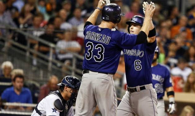 Colorado Rockies' Corey Dickerson is greeted by Justin Morneau, left, after blasting a three-run home run against the San Diego Padres in the sixth inning of a baseball game Monday, Aug. 11, 2014, in San Diego. (AP Photo/Lenny Ignelzi)