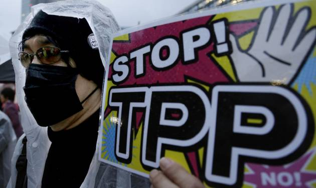 """A protester holds a placard during a rally against the Trans-Pacific Partnership (TPP) in Tokyo, Tuesday, April 22, 2014. In Japan and elsewhere, there are concerns over making politically difficult market-opening concessions without reassurance that Obama will have the """"fast track"""" authority to get congressional approval for TPP. Critics of the plan have balked at granting such power for a trade deal whose contents have been kept largely secret as a precondition for joining. (AP Photo/Shizuo Kambayashi)"""