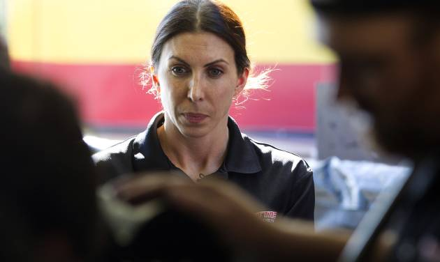 ADVANCE FOR WEEKEND EDITIONS, MAY 12-13 - In this photo taken, Jan. 20, 2012, Alexis DeJoria watches as her crew works on her race car in Jupiter, Fla. She is a tattooed mom, an heiress to a billion-dollar empire, and she has been drag racing competitively since 2005. DeJoria, 34, is a ranked National Hot Rod Association driver and the second woman to win a National event in funny car. (AP Photo/J Pat Carter)