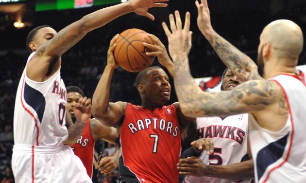 Toronto Raptors' Kyle Lowry (7) is blocked by Atlanta Hawks' Jeff Teague (0), DeMarre Carroll (5), and Pero Antic (6)  during overtime of their NBA basketball game Tuesday, March 18, 2014, in Atlanta. Atlanta won 118-113. (AP Photo/David Tulis)