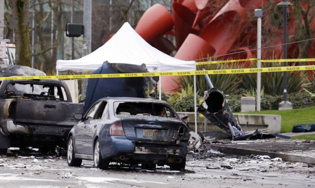 Caution tape surrounds the charred wreckage of a news helicopter and two vehicles after the chopper crashed into a city street near the Space Needle, Tuesday, March 18, 2014, in Seattle. Two people were killed and another was critically injured, according to the Seattle Fire Department. (AP Photo/Elaine Thompson)