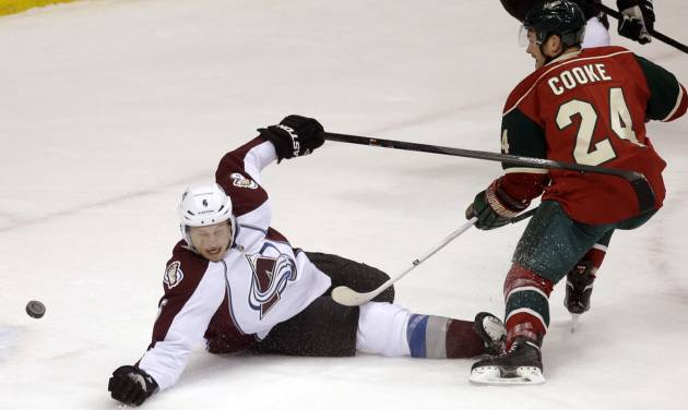 Minnesota Wild's Matt Cooke shoots a puck past Colorado Avalanche's Erik Johnson, which goalie Semyon Varlamov stopped in the first period of an NHL hockey game, Saturday, Jan. 11, 2014, in St. Paul, Minn. (AP Photo/Jim Mone)