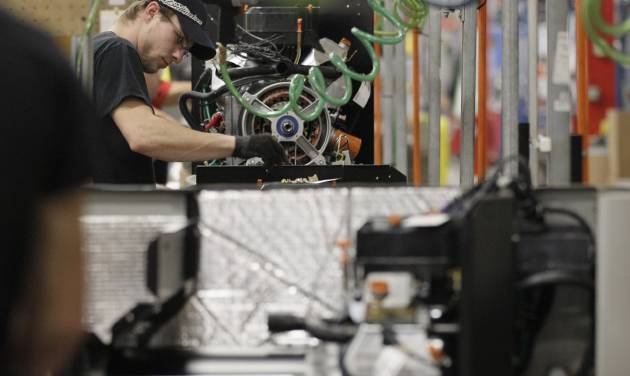 In this Nov. 16, 2012 photo, an employee works on assembly line at Generac Power Systems, Inc., in Whitewater, Wis. After U.S. manufacturing shrunk in November, it grew slowly in December and hiring increased, a sign of modest economic momentum heading into the new year. (AP Photo/Nam Y. Huh)